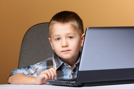 Computer addiction child boy with laptop computer brown background