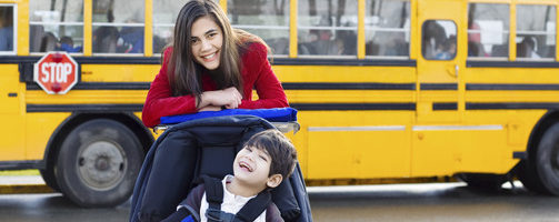 Big sister with disabled brother in wheelchair by school bus